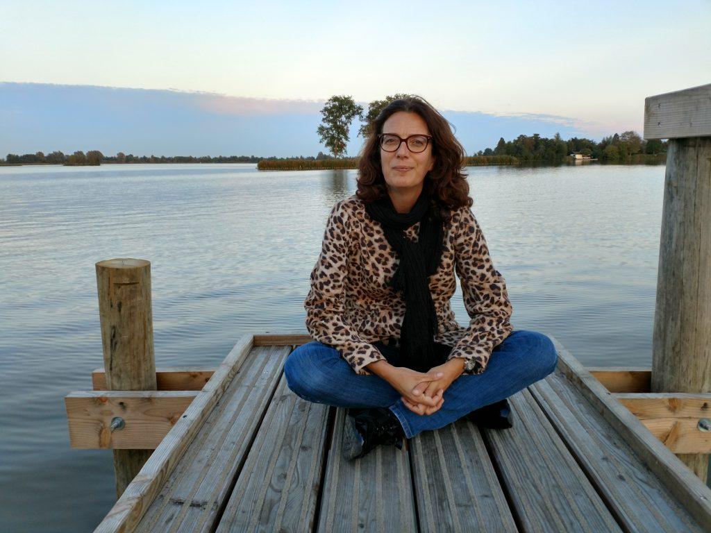 Natalie zittend op een aanlegsteiger aan een meer