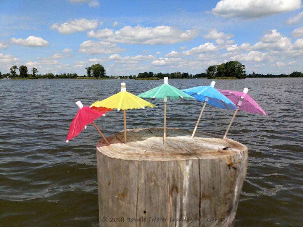 Gekleurde parasols aan het water